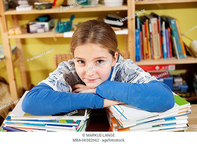 Girl, 10 years old, doing homework, leans on a stack of books