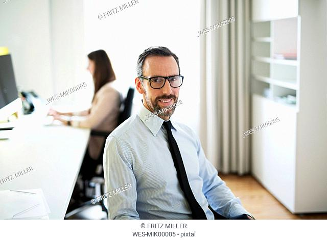 Portrait of confident businessman in office with employee in background