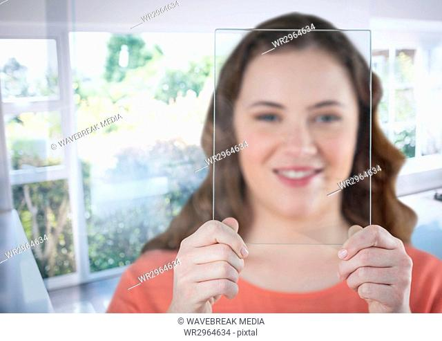 Woman holding glass screen by sunny window