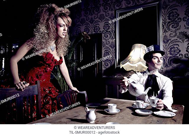 A young woman wearing a red dress looking at a young man sat by a table pouring a cup of tea wearing a top hat