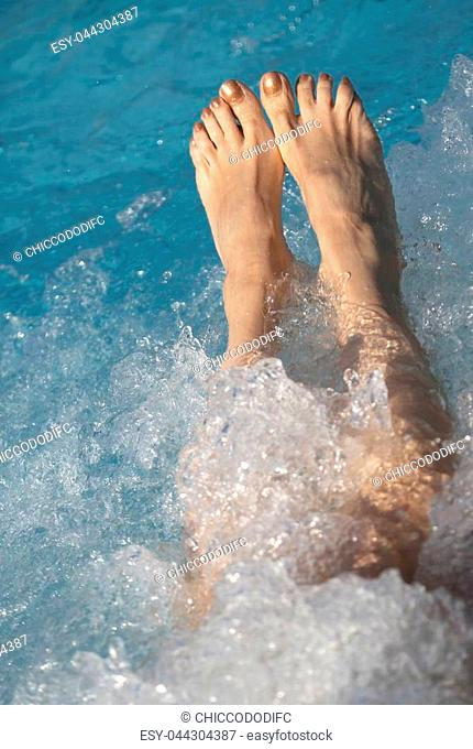two feet of a young woman during the hydromassage session in the spa pool