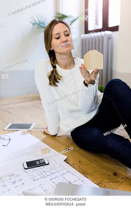 Woman sitting on the floor with blueprint looking at house model