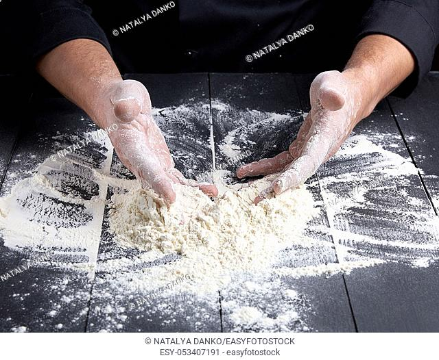 white wheat flour scattered on a wooden wooden table, the chef in uniform uniforms hands the product