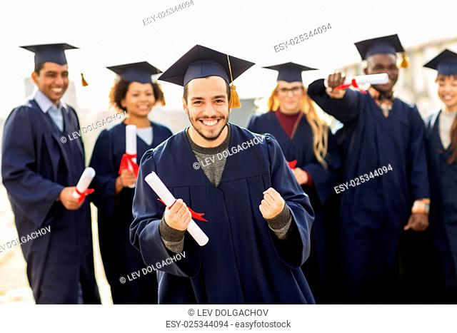 education, gesture and people concept - group of happy international students in mortar boards and bachelor gowns with diplomas celebrating successful...