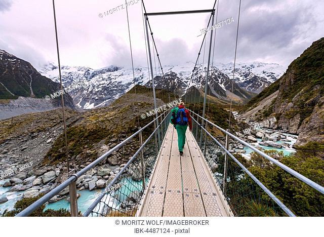 Hiker proceeds suspension bridge over River Hooker, Hooker Valley, Mount Cook National Park, Canterbury Region, New Zealand