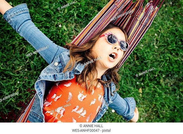 Portrait of singing girl wearing sunglasses lying in hammock