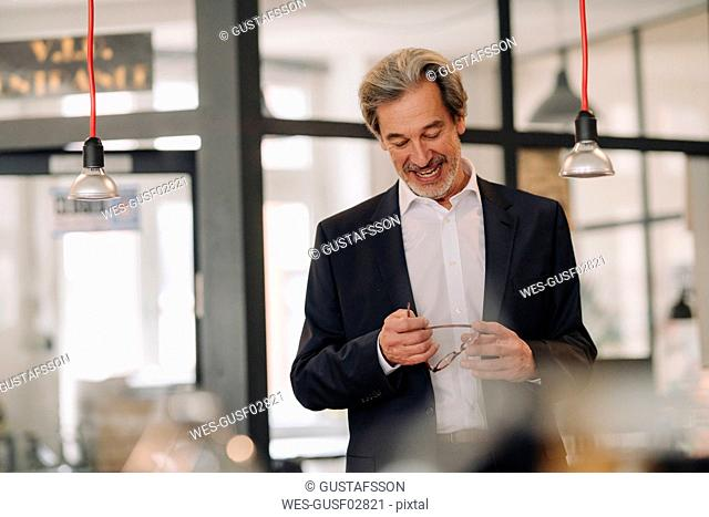 Happy senior businessman in office holding glasses