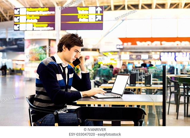 Shot of a handsome business freelance man talking on a mobile phone while reviewing documents sitting in airport cafe out of the office