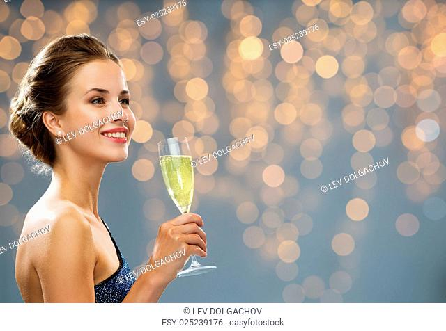 party, drinks, holidays, luxury and celebration concept - smiling woman in evening dress with glass of champagne over black background