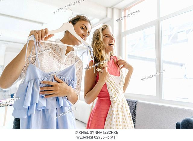 Two happy young women holding dresses