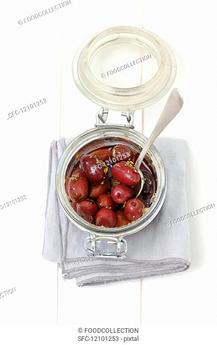 Pickled kalamata olives with oregano in a glass jar