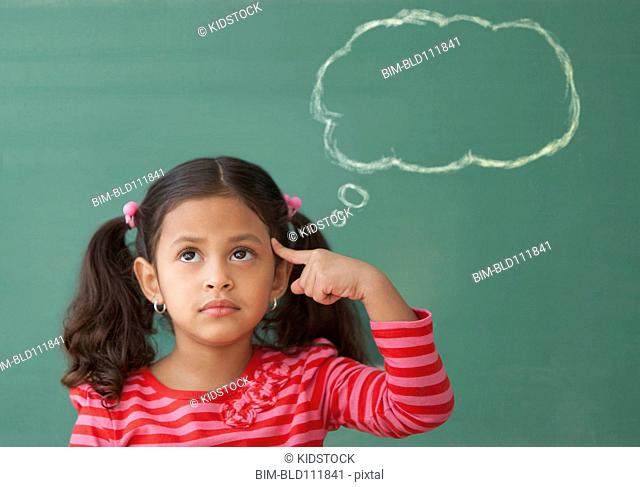 Hispanic girl at chalkboard with thought bubble