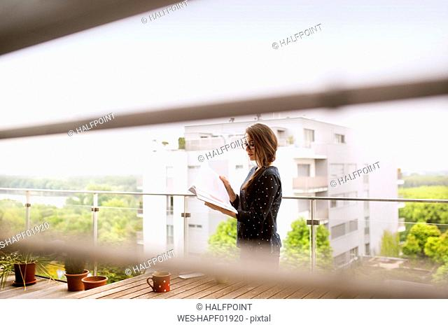 Woman with notebook standiing on balcony