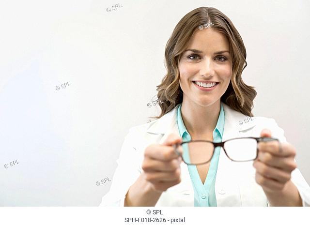 Female optician holding glasses