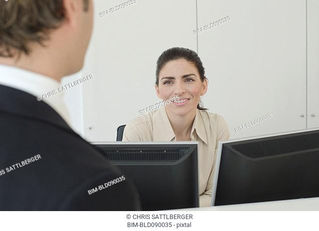 Hispanic businessman talking to receptionist