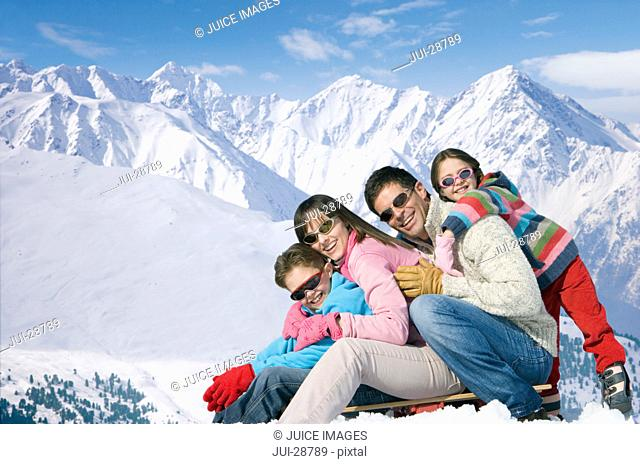 Smiling family sitting on sled on mountain top