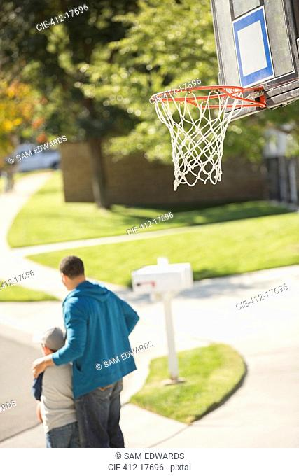 Father and son hugging near basketball hoop