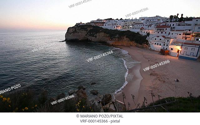 View of Carvoeiro village at sunset with beach and rocky coast, Algarve, Portugal, Europe