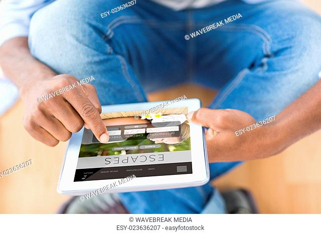 Composite image of businessman using digital tablet in creative office