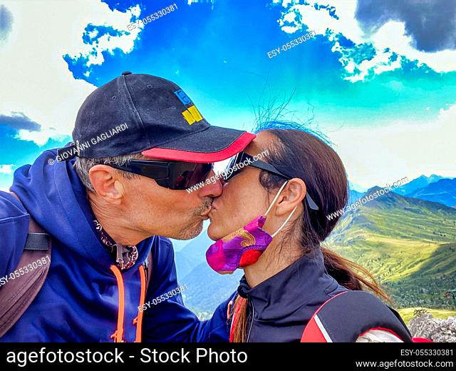 Happy couple on a mountain excursion kissing each other