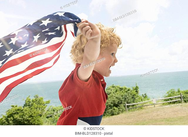 Caucasian boy playing with American flag