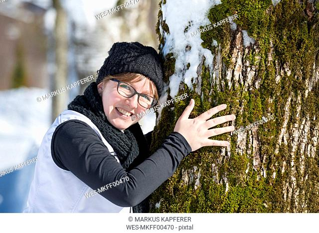 Portrait of smiling woman hugging a tree in winter