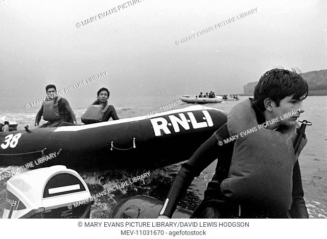 Schoolboys in motor-powered inflatable dinghies on the sea near Atlantic College (United World College of the Atlantic), St Donat's Castle, Llantwit Major
