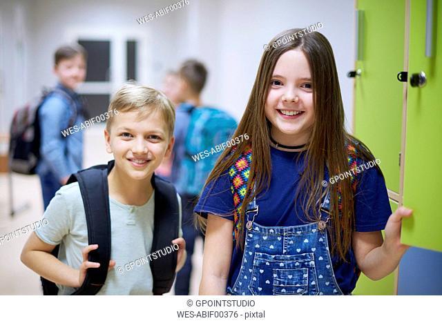 Portrait of smiling schoolboy and schoolgirl at lockers in school