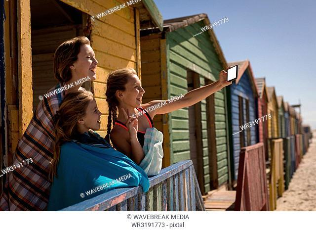 Siblings taking selfie with mobile phone at beach