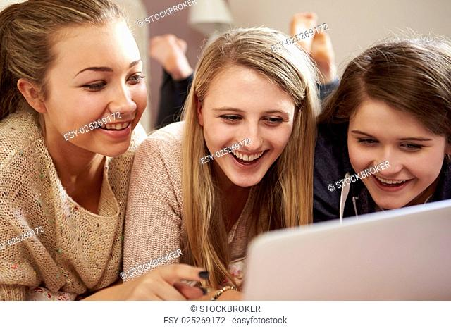Three Teenage Girls Using Laptop In Bedroom