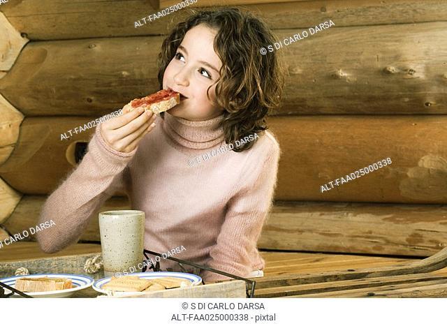 Girl having snack, looking away