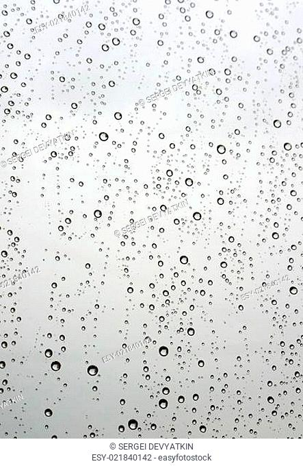 Drops of rain on the inclined window (glass)