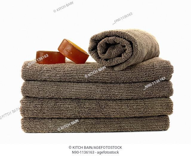 A stack of bath towels and soap isolated against a white background