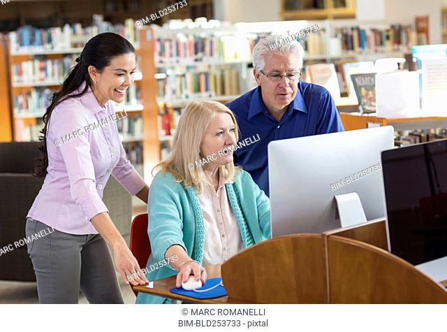 Older man and women using computer in library