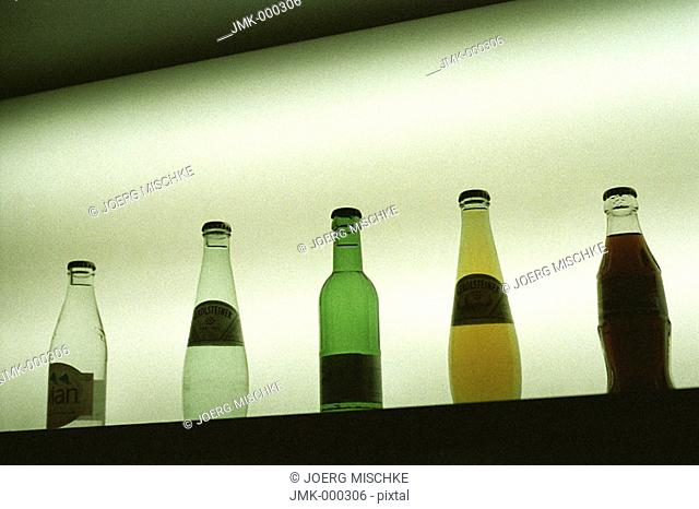 Group of bottles with table water or soda or soft drinks on a board, light in the background