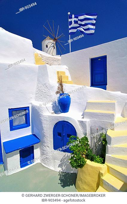 Blue and yellow inner courtyard with stairs, Greek flag blowing in the wind, typical Cycladic architecture, windmill behind, Oia, Ia, Santorini, Cyclades