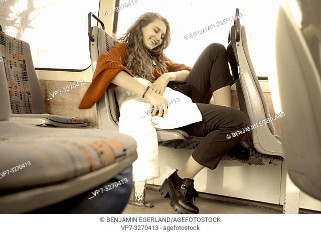 young woman sitting in public transport, putting phone back in pocket of white jacket, in city Cottbus, Brandenburg, Germany