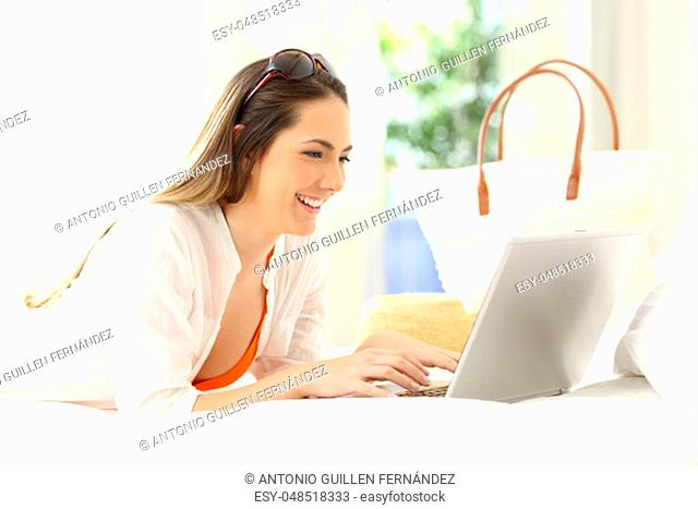 Happy woman using a laptop lying on a bed of an hotel room on summer vacations