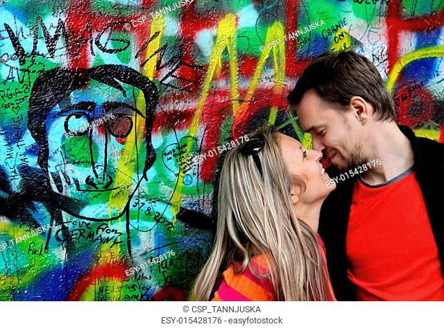 John Lennon wall in Prague and young beautiful couple in love