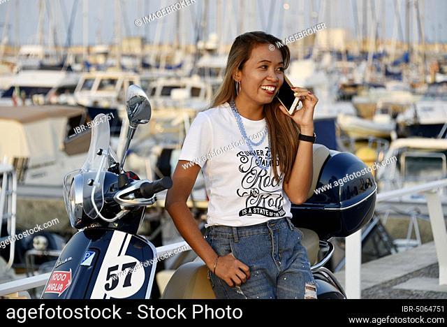 Woman with Vespa 125 Primavera in the port of Penelope, Porto Senigallia, Senigallia, province of Ancona, Marche, Italy, Europe
