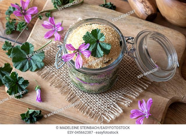 A jar filled with wild common mallow flowers and leaves and cane sugar, to prepare herbal syrup against cough