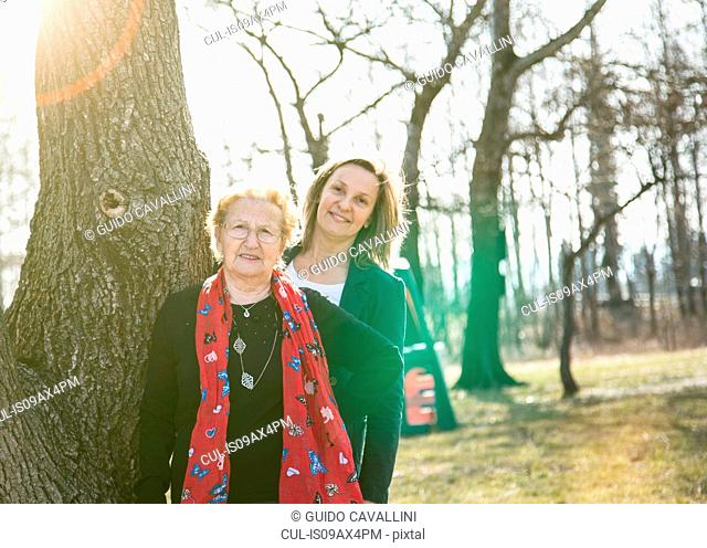 Adult daughter standing behind mother by tree looking at camera smiling