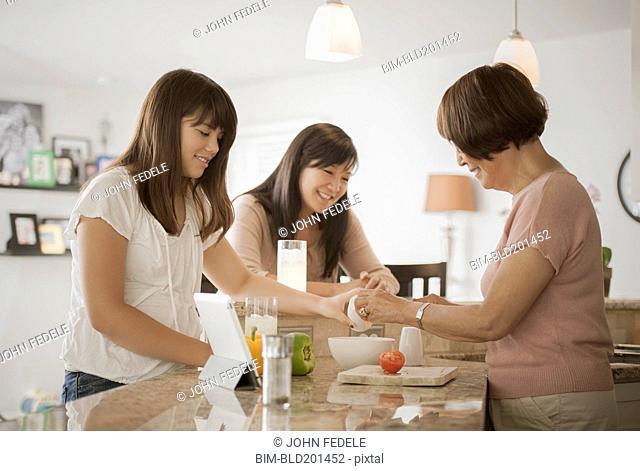 Grandmother, mother and daughter preparing food