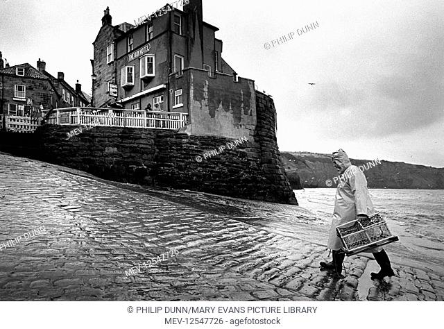 A fisherman carries a lobster pot up the cobbled slipway at Robin Hood's Bay, North Yorkshire, England. It is a wet winter's day and he wears wellington boots...