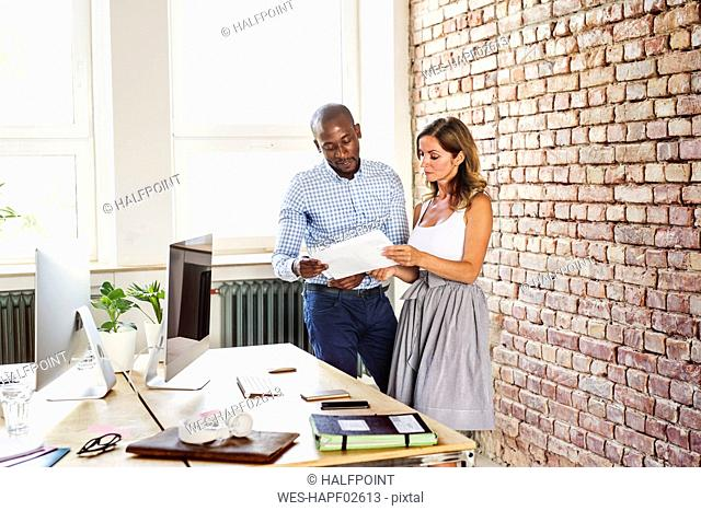 Two colleagues discussing paper at desk in office