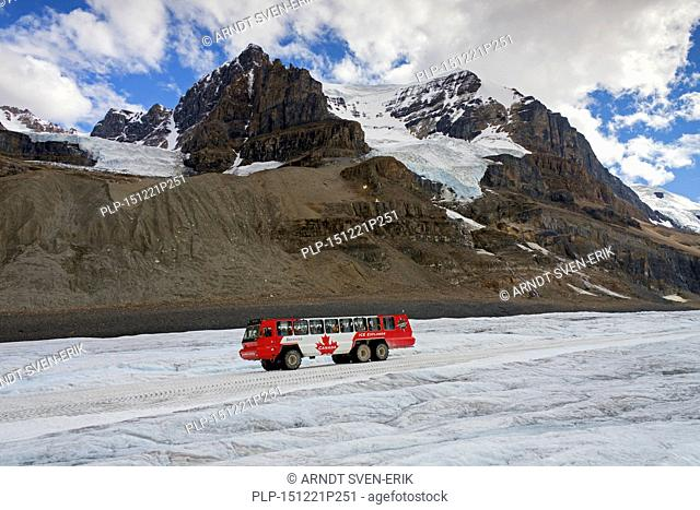 All-wheel-drive, three axle snow coach with tourists on the retreating Athabasca Glacier, part of the Columbia Icefield in the Canadian Rockies