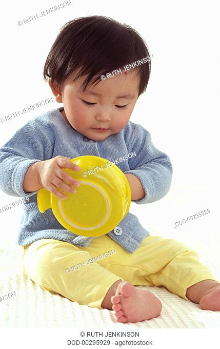 Baby sitting on the floor holding a yellow plastic bowl