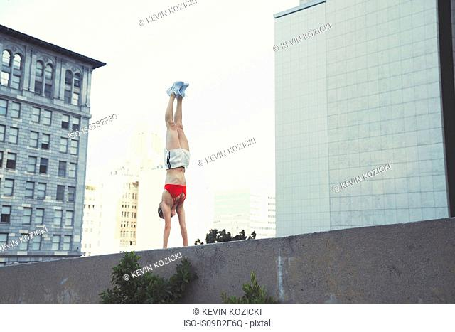 Young woman doing handstand on wall outdoors