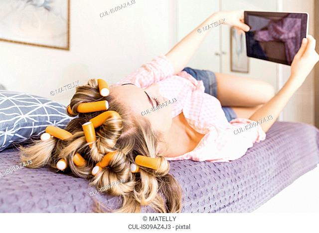 Young woman with foam rollers in hair, lying on bed, using digital tablet