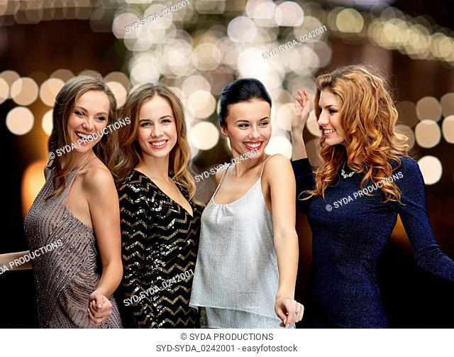 happy young women dancing over night lights